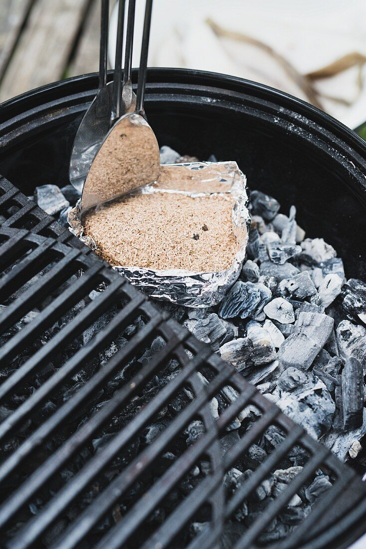 A smoked mixture being placed on glowing coals in a charcoal barbecue