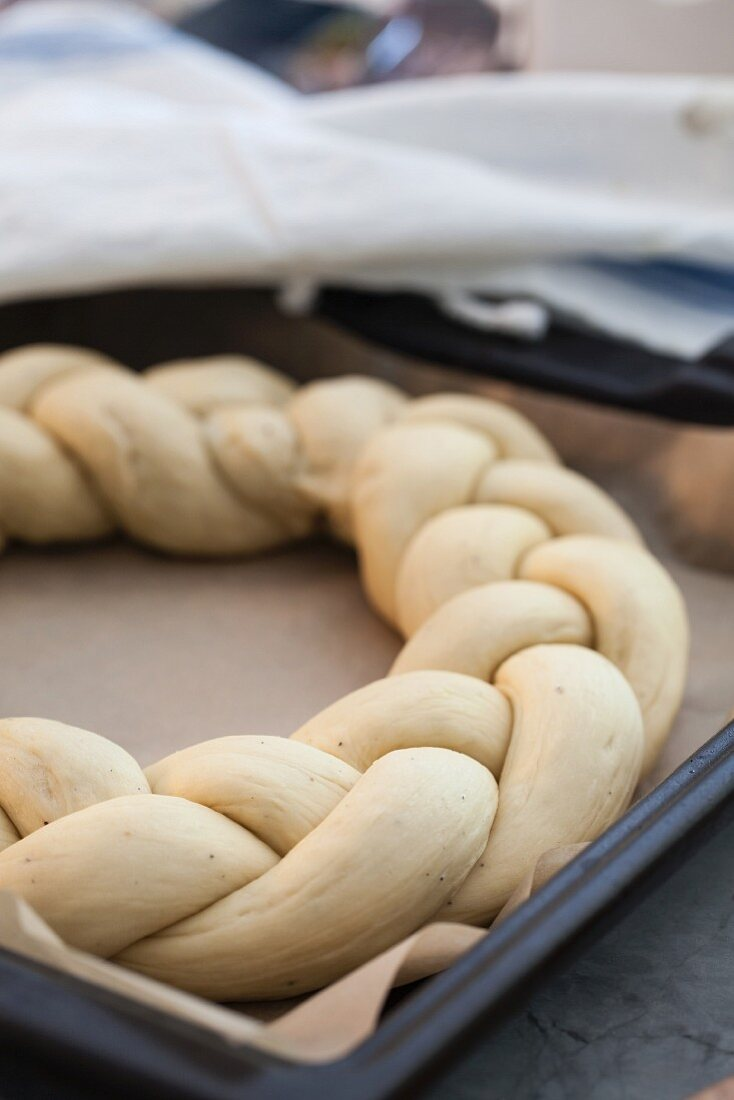 An unbaked bread wreath on a baking tray