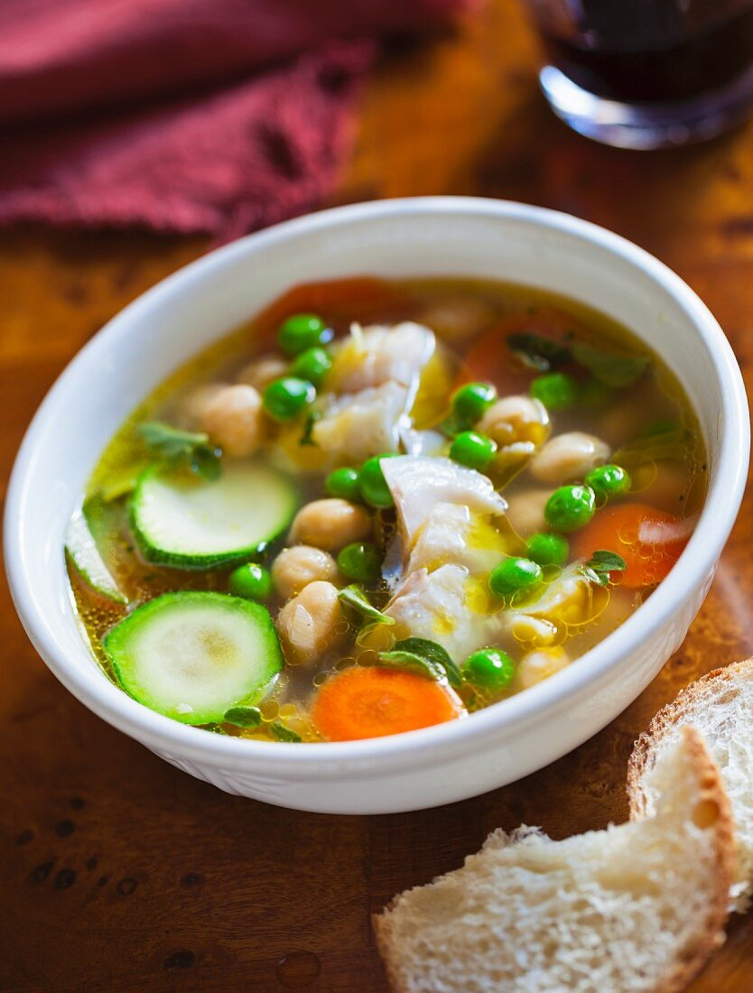 Halibut soup with courgette, peas, carrots and chickpeas