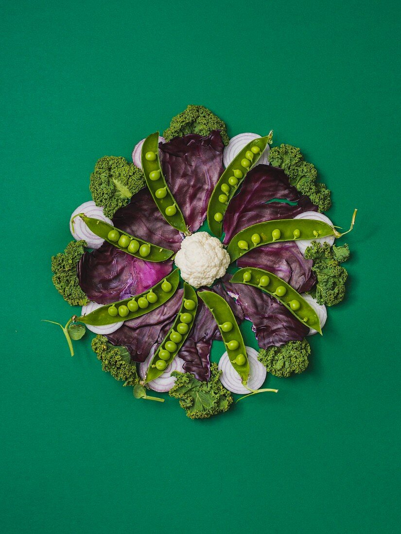 Various vegetables in a flower shape arranged on a green surface