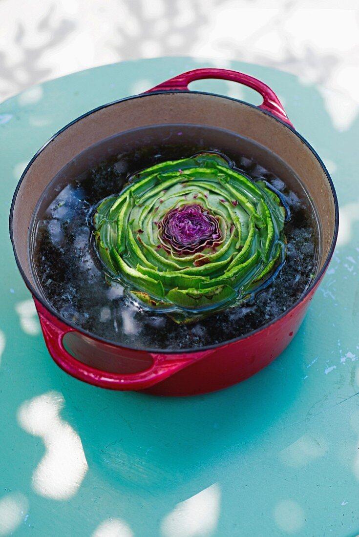 An artichoke in a pot of water