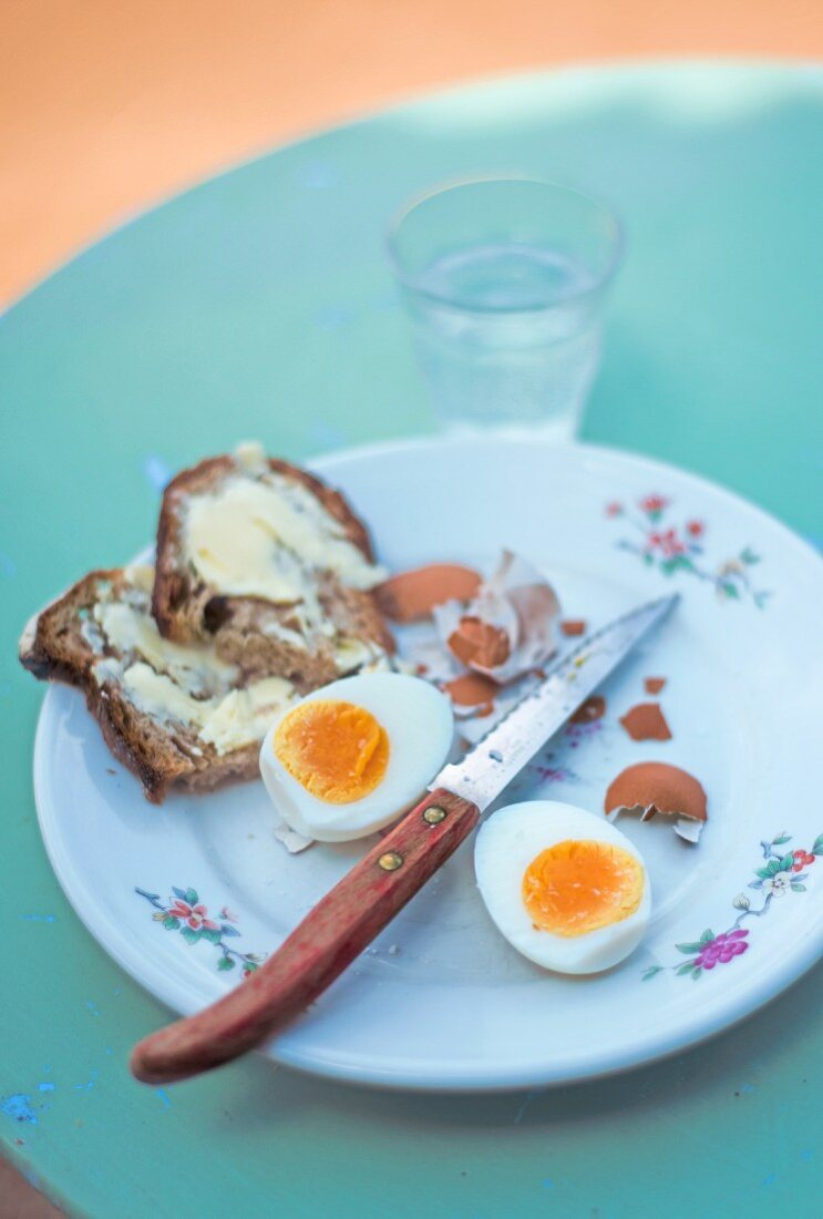 A hard-boiled egg and a slice of buttered bread on a plate