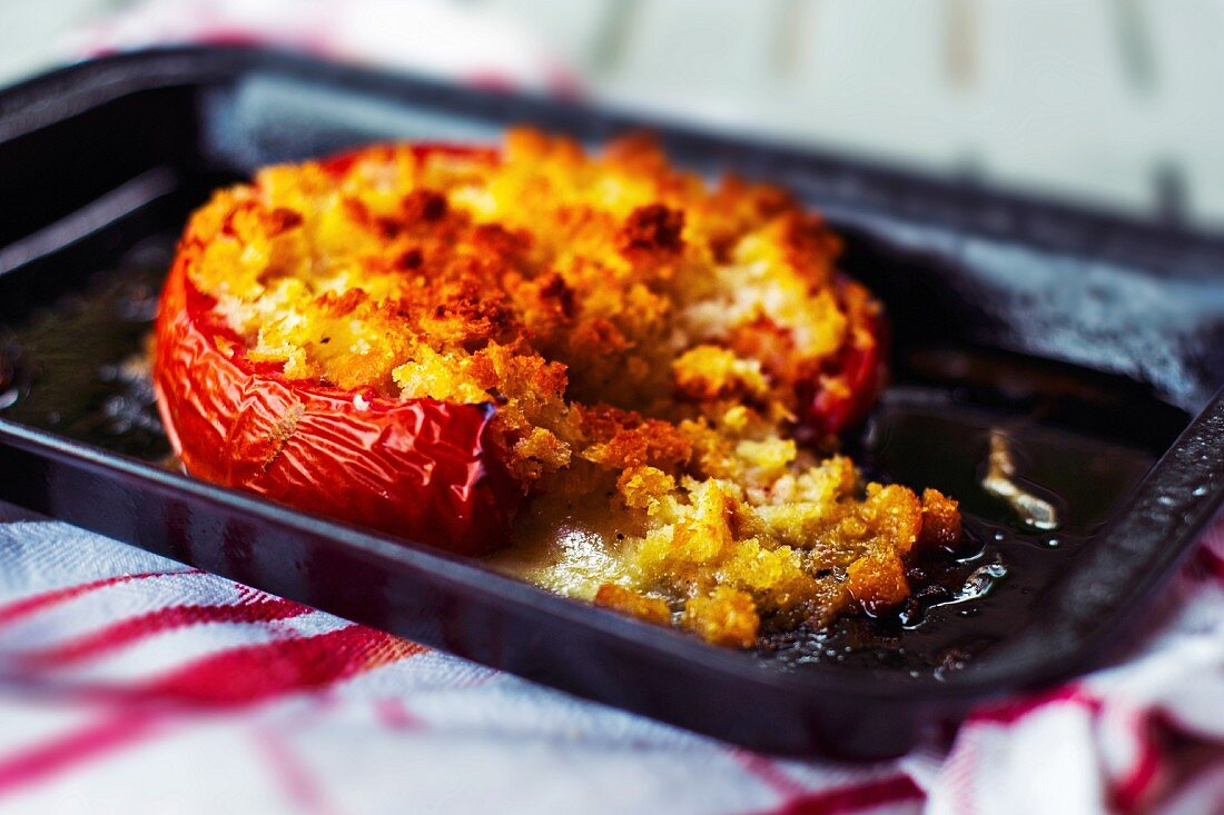 A roasted tomato filled with breadcrumbs on a baking tray