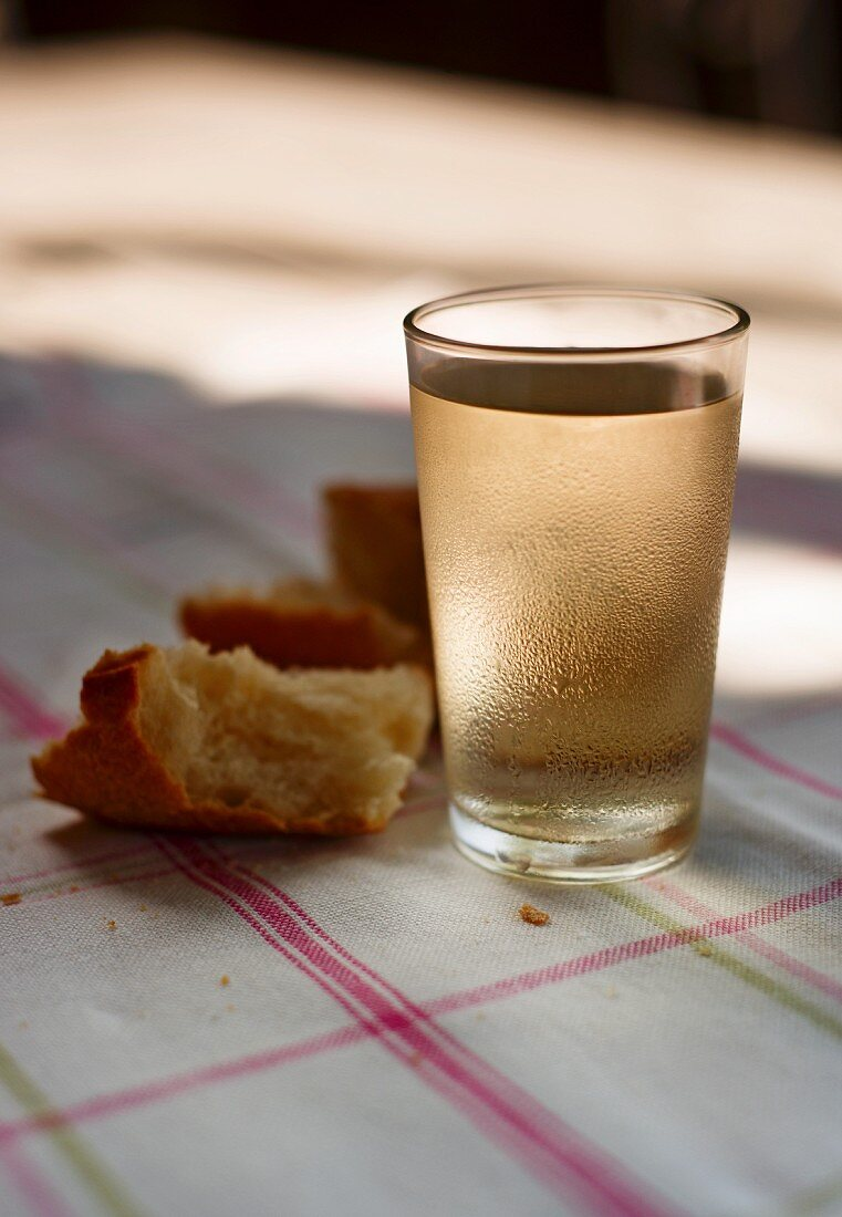 A glass of white wine and bread on a sunny table