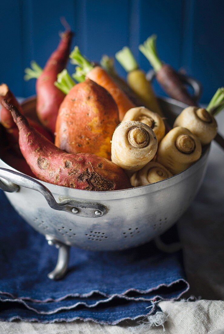 Parsnips, sweet potatoes and carrots in a colander