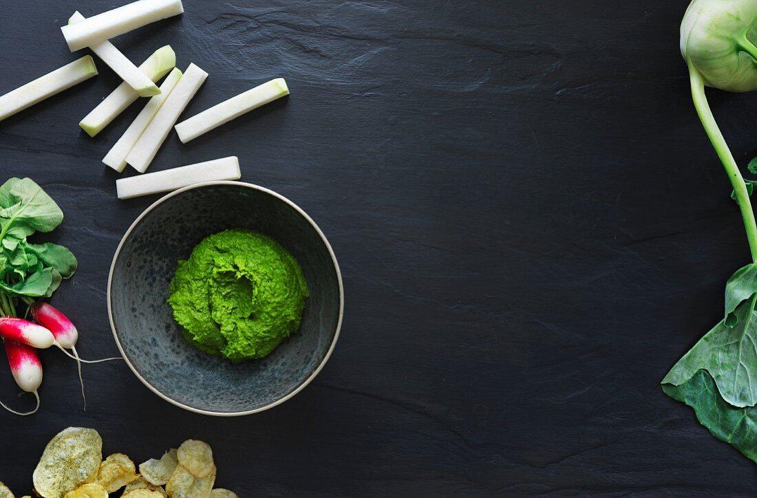 A green kale dip, kohlrabi sticks and potato crisps