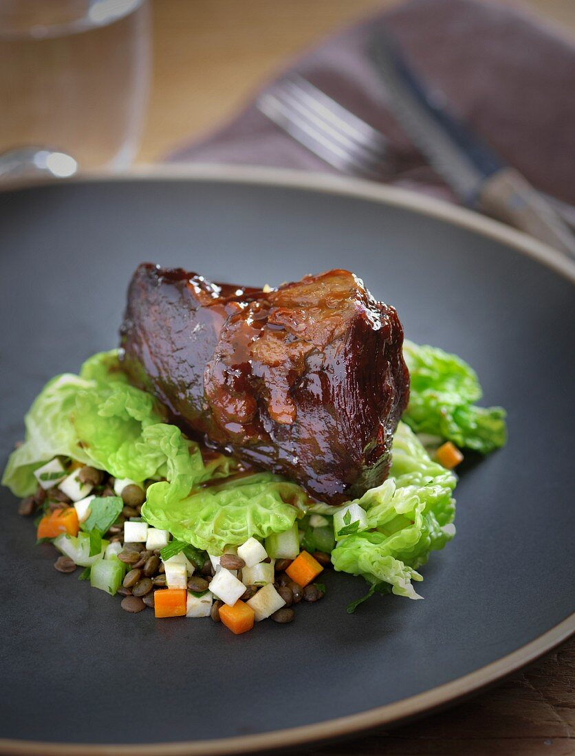 A veal cheek on buttered savoy cabbage and a lentil medley