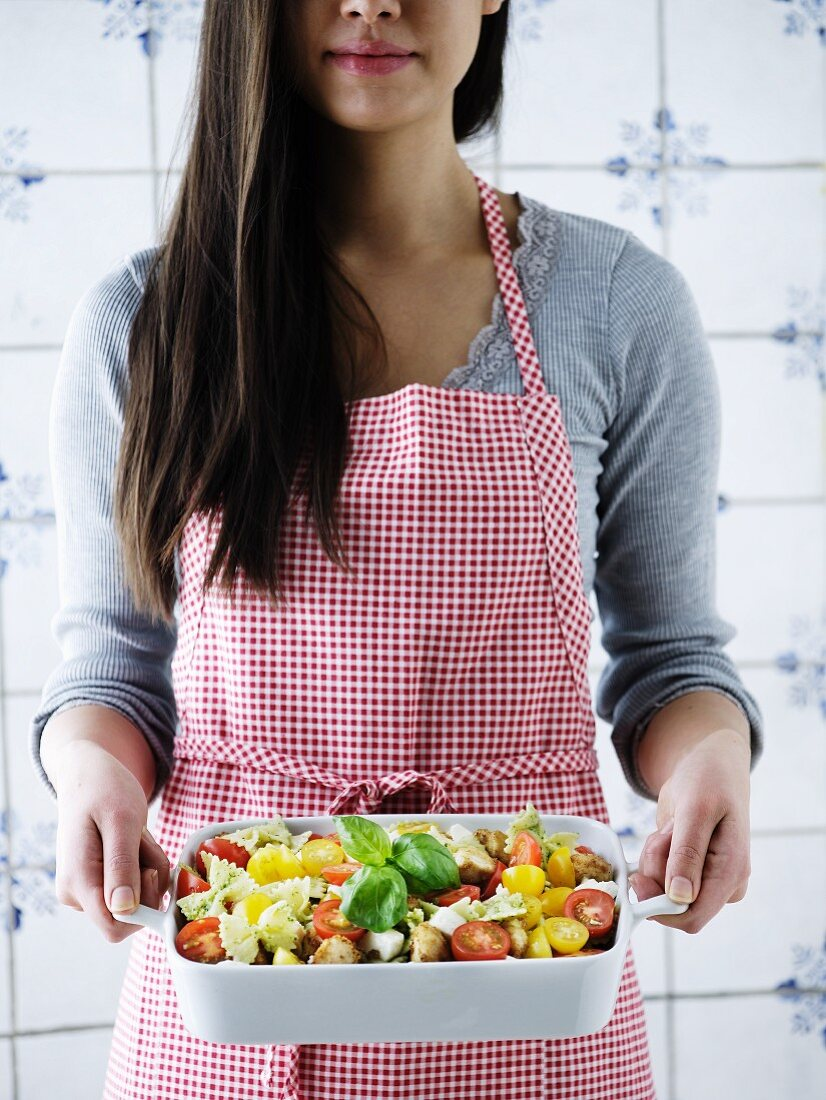 A woman holding a pasta bake with tomatoes