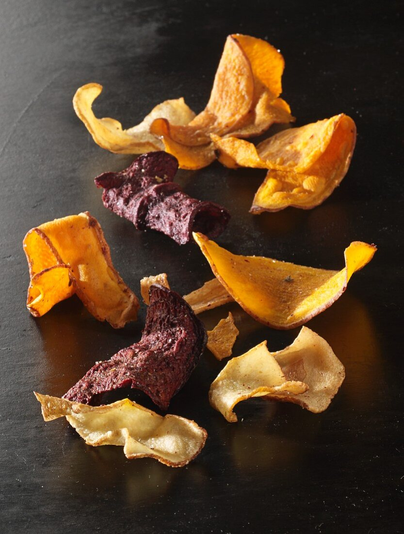 Vegetable chips on a black surface