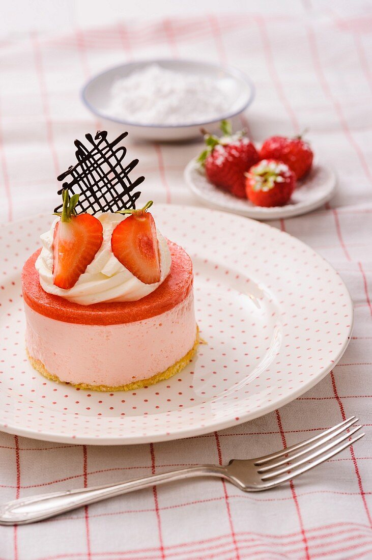 A strawberry tartlet with a chocolate lattice decoration