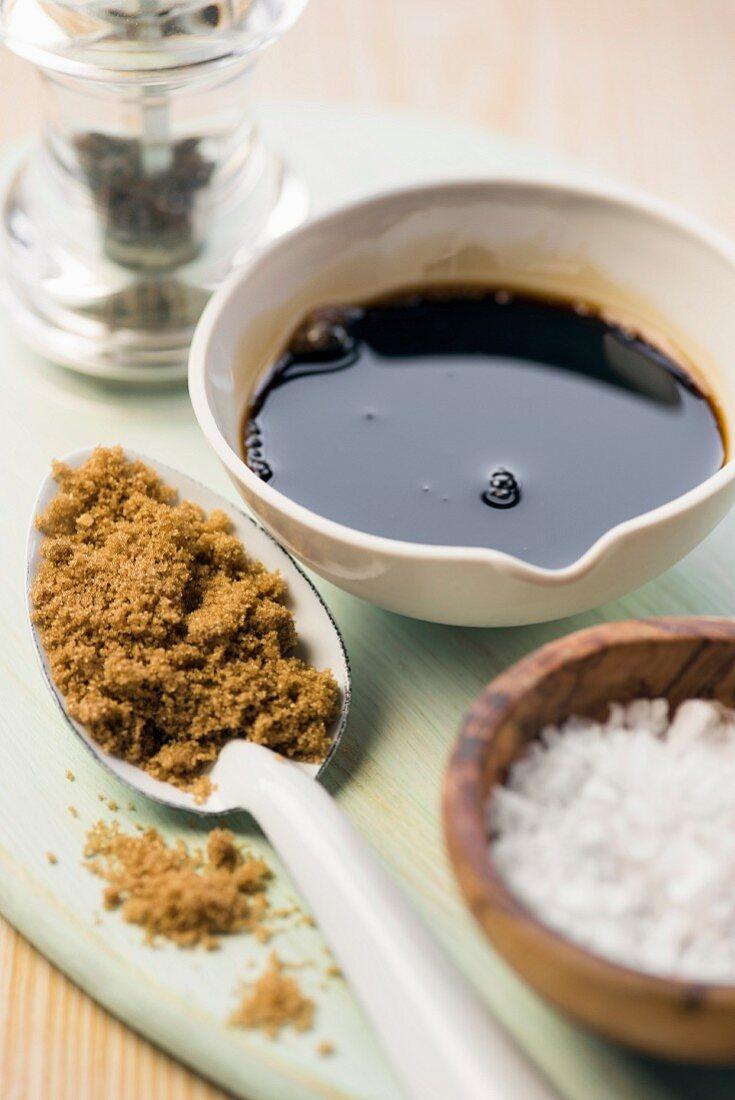 An arrangement of balsamic vinegar, pepper, brown sugar and salt