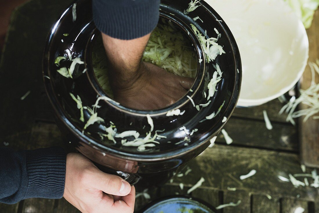 Cabbage being squashed into a pot