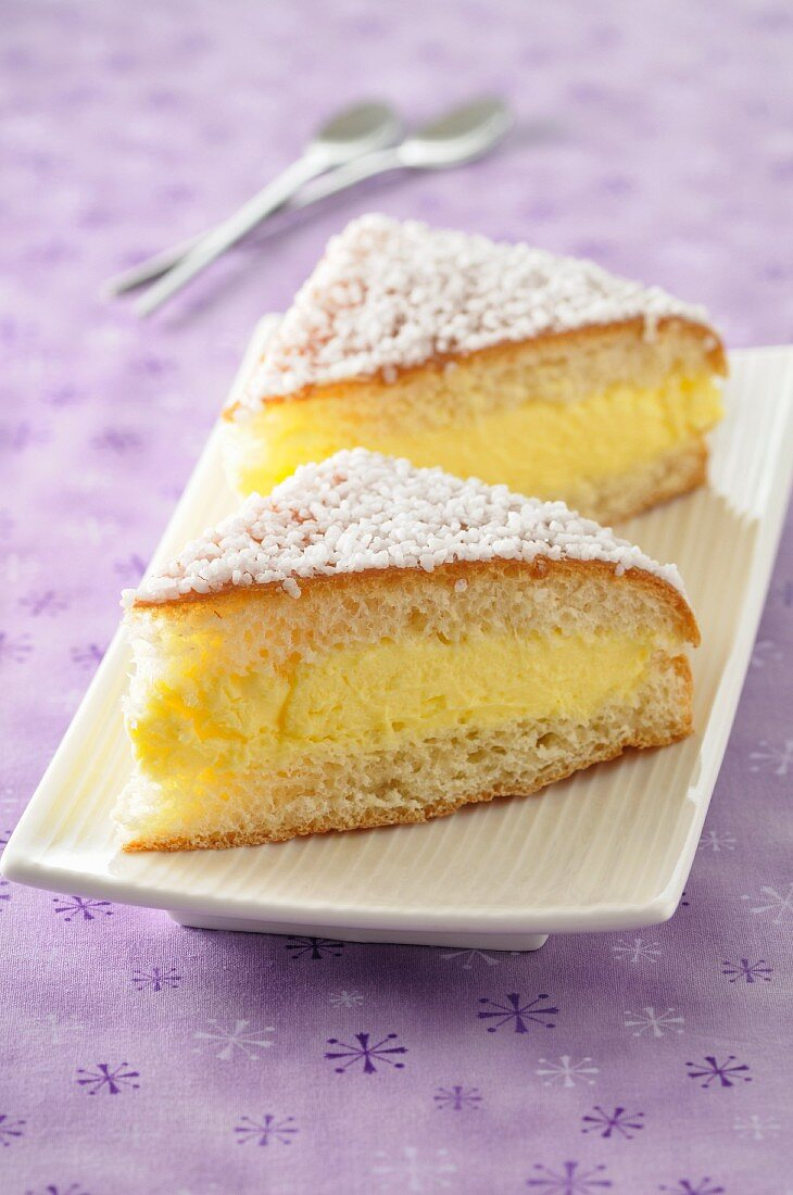Two slices of vanilla pudding cake with grated coconut