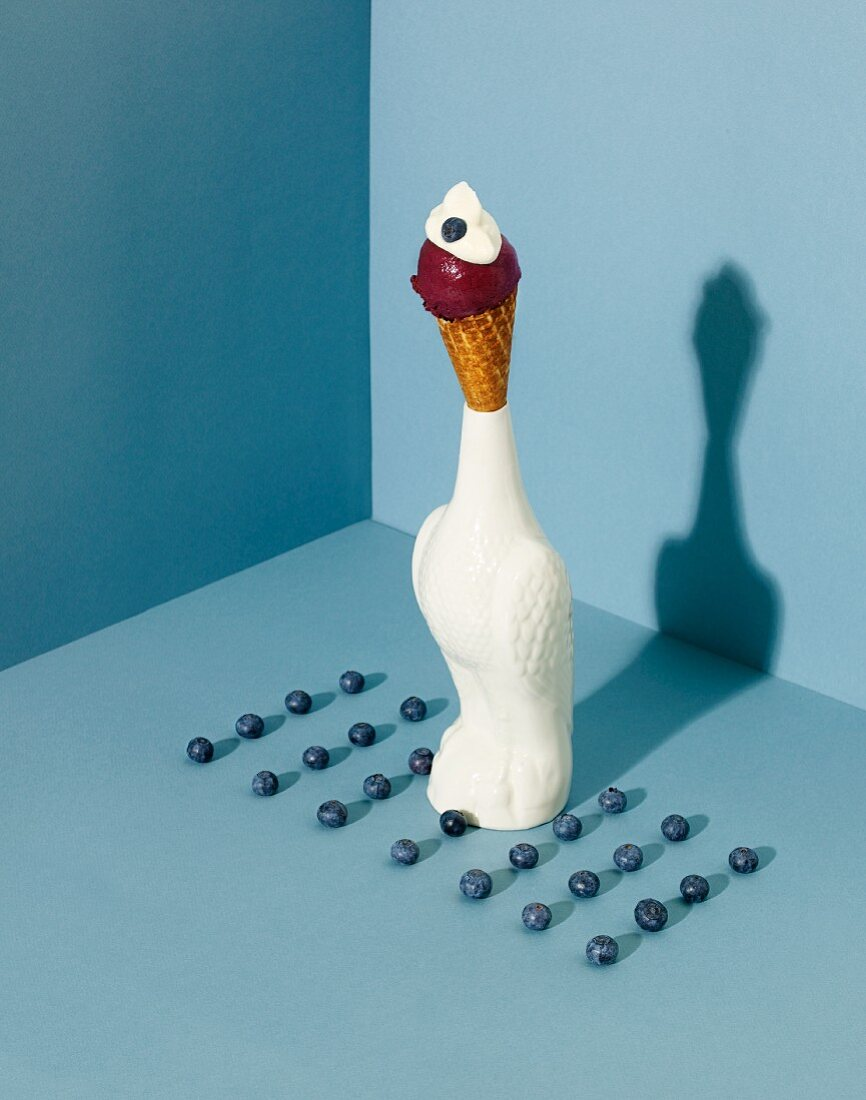 An ice cream cone with blueberry and vanilla ice cream in a bird-shaped holder