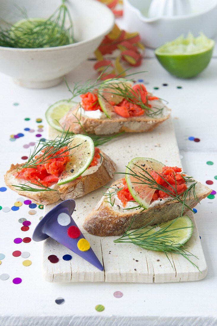 Baguette slices topped with salmon, mayonnaise, lime, and dill