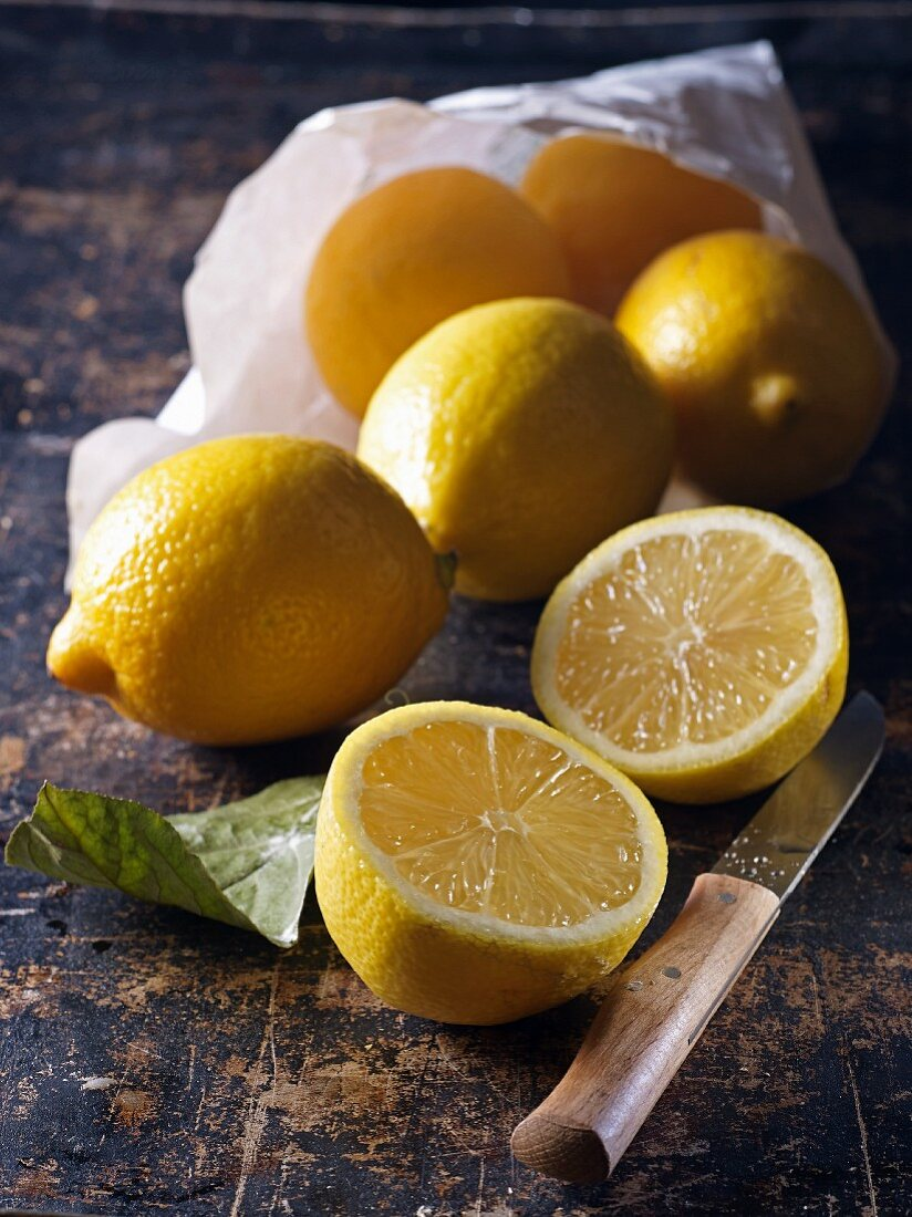 Lemons in a paper bag with one in the foreground halved