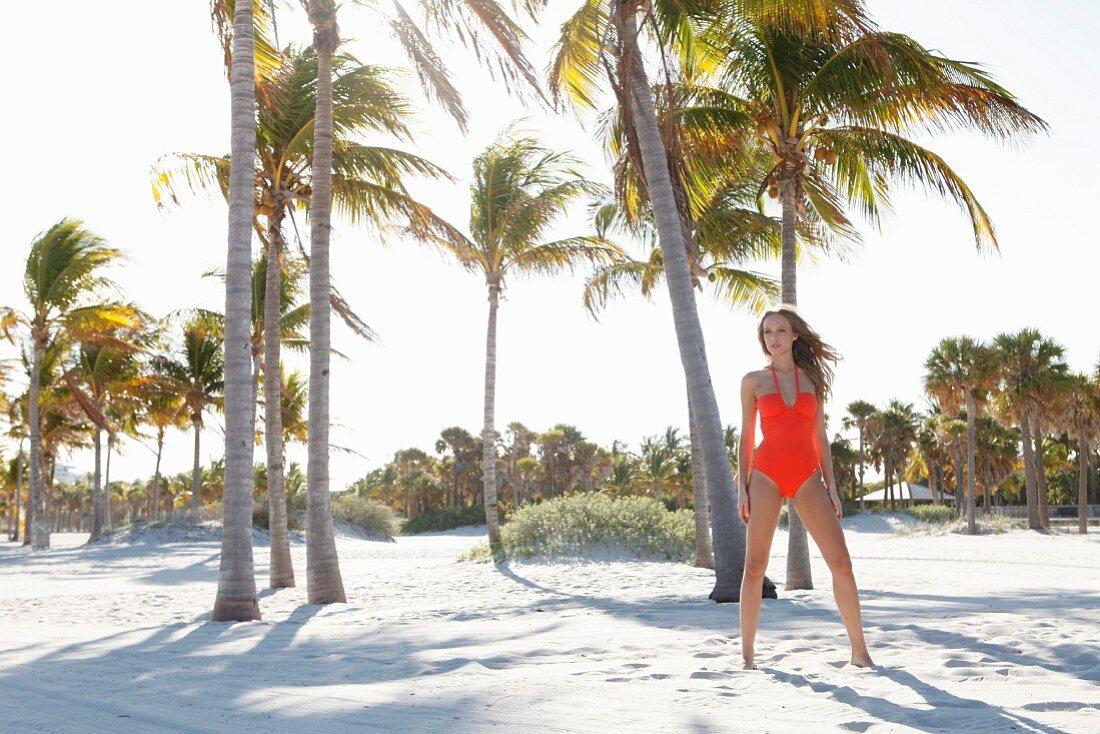 Junge blonde Frau in orange Badeanzug steht am Strand vor Palmen