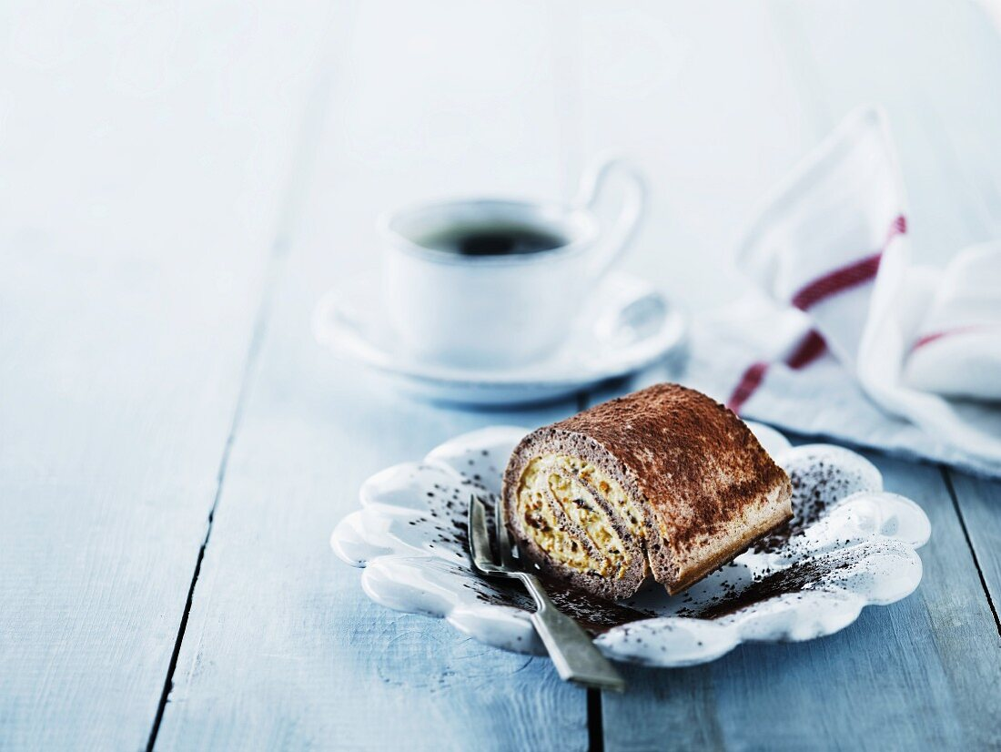 A creamy Swiss roll served with a cup of coffee