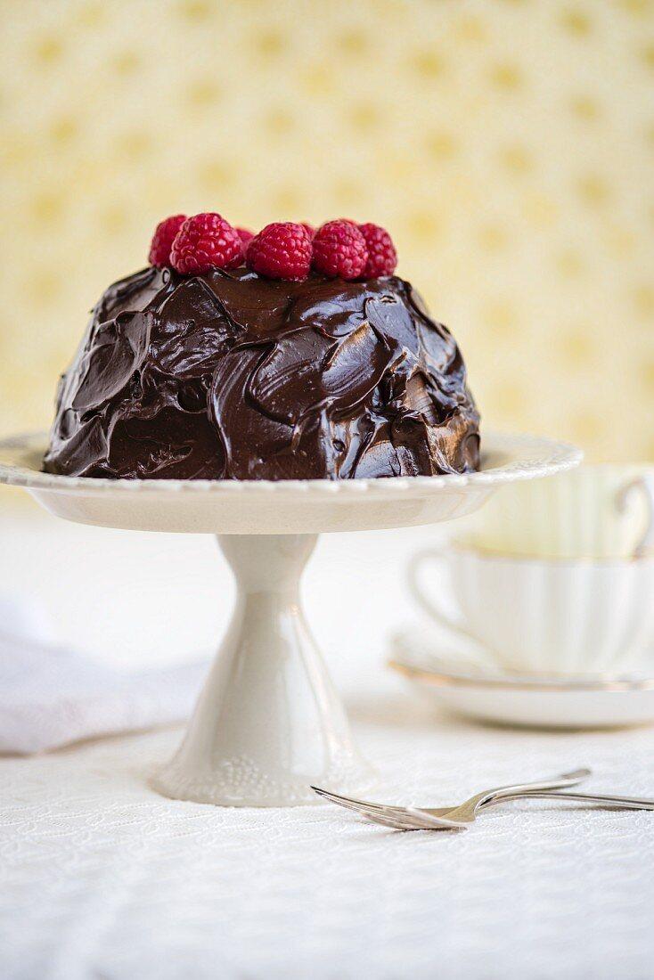 Gluten-free cake with avocado, cocoa and honey glaze and fresh raspberries