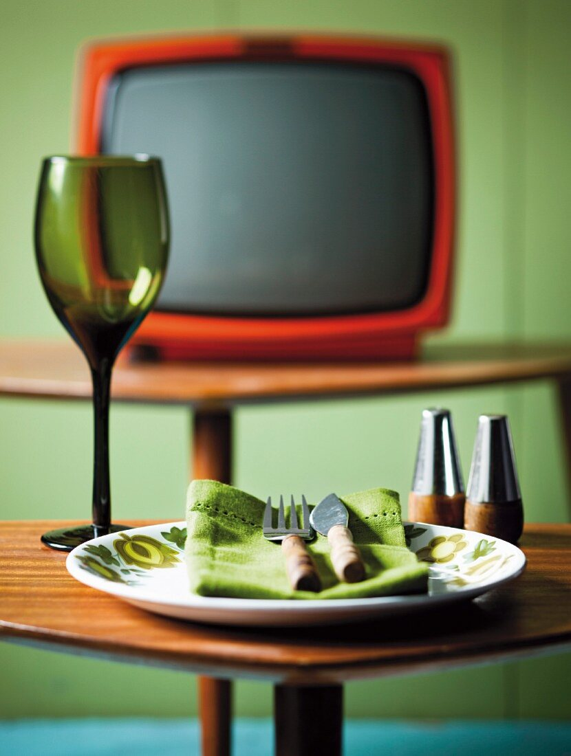 An empty plate with cutlery and a wine glass in front of the television