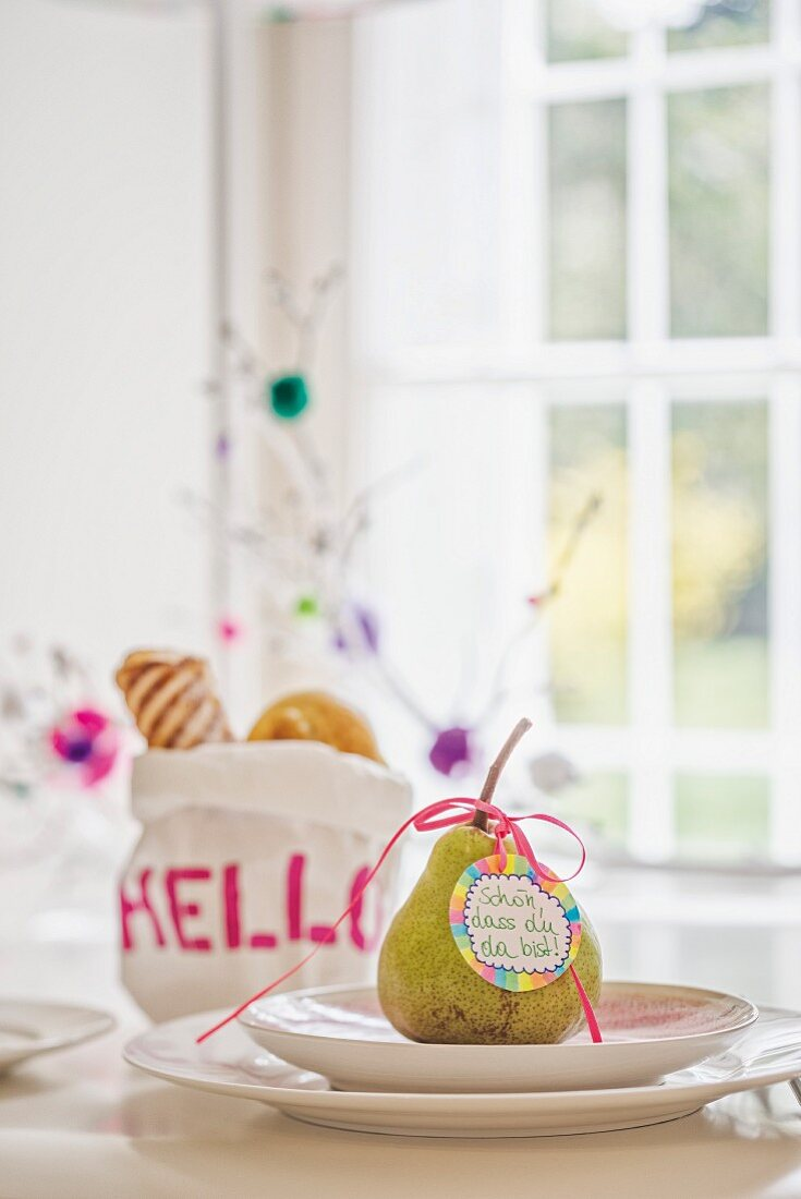Tag with welcome message tied to pear on place setting