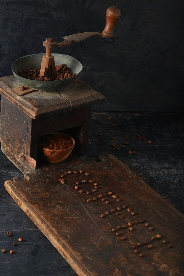 And antique coffee grinder in front of the word 'Coffee' written in coffee beans