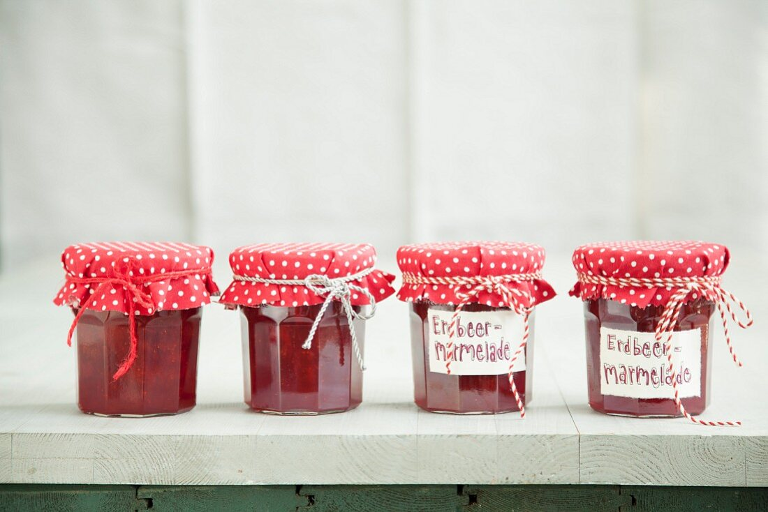 Jars of strawberry jam with homemade fabric lid covers