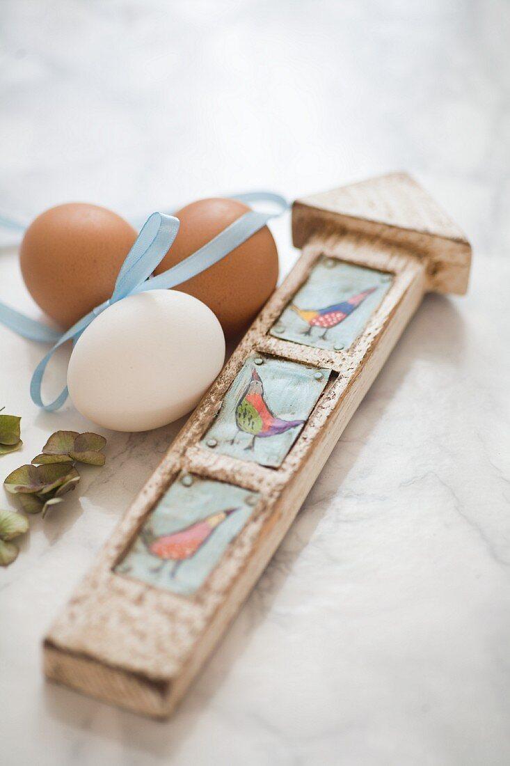 Hühnereier mit Dekoband und Holzwegweiser auf Marmoruntergrund