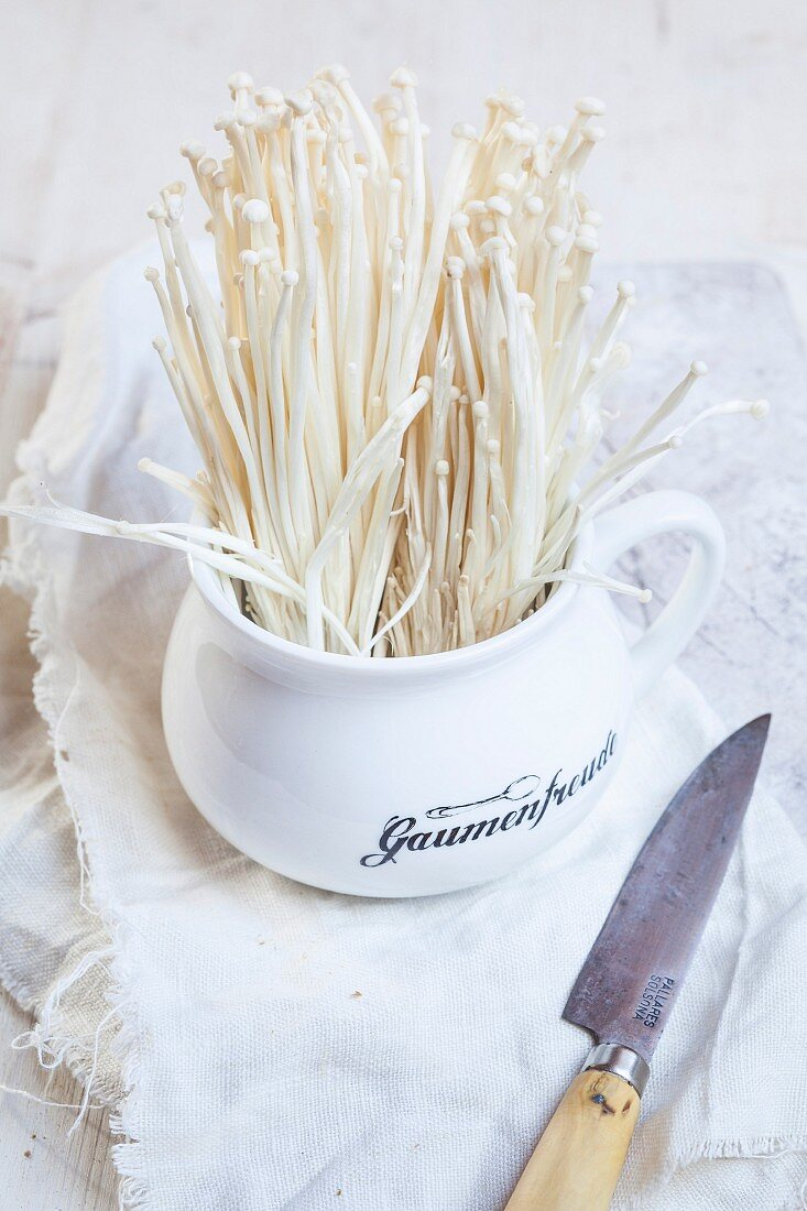 A cup of fresh enoki mushrooms