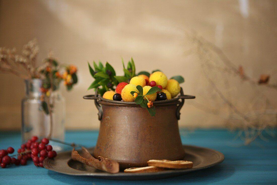 Various winter fruit in a metal pot