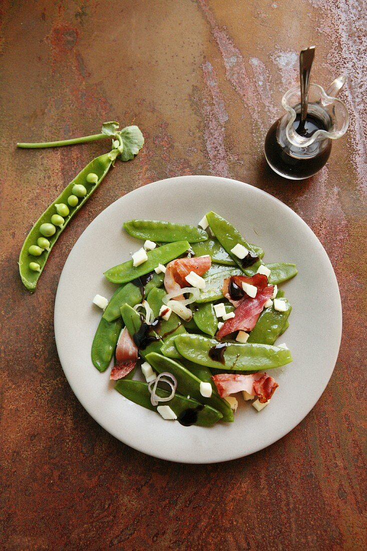 Mangetout salad with cubes of cheese, onion, bacon and balsamic vinegar
