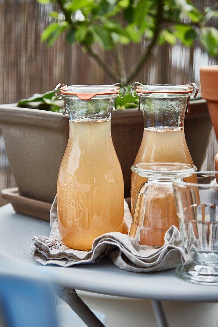 Rhubarb syrup in flip-top carafes