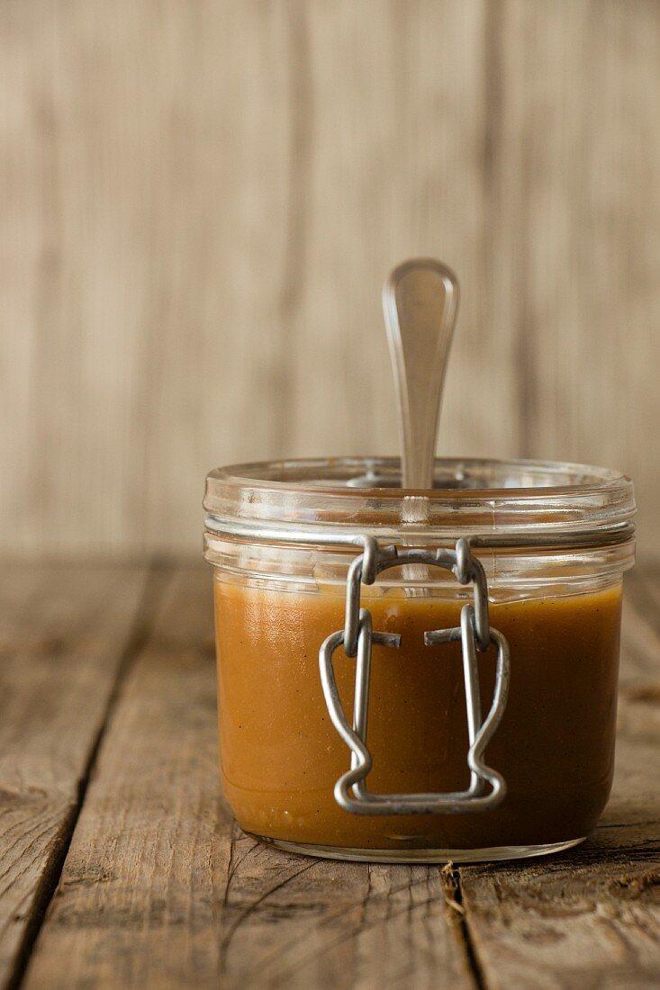 Dulce de leche in a flip-top jar with a spoon