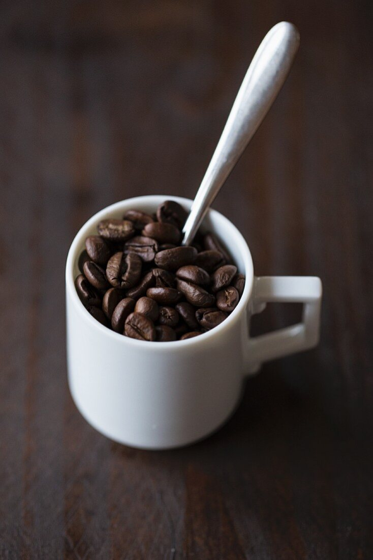 Coffee beans and a spoon in an espresso cup