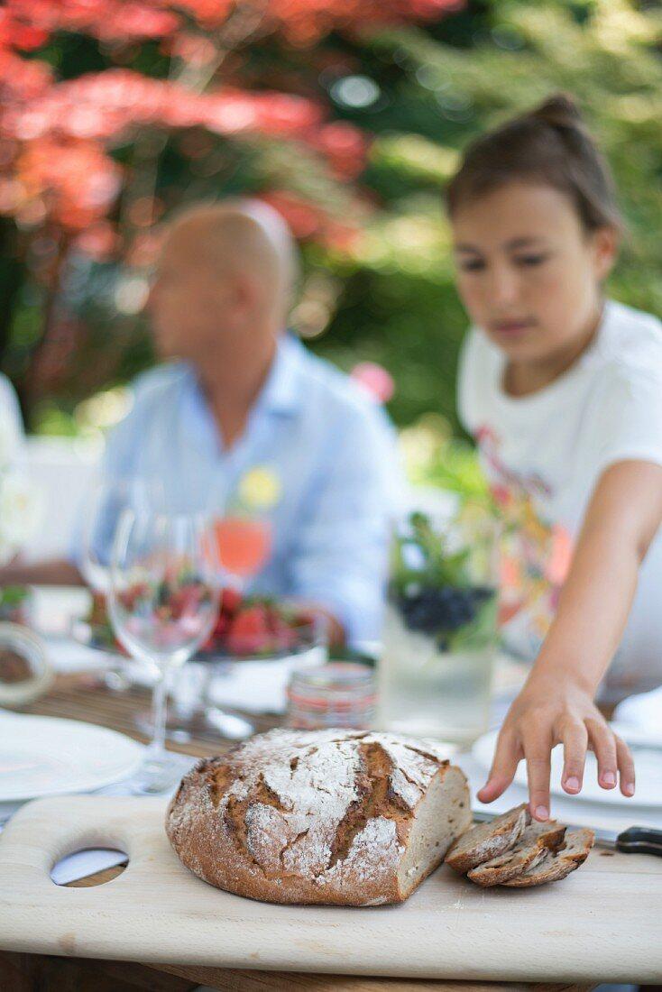 Girl picking up slice of crusty bread at brunch in garden