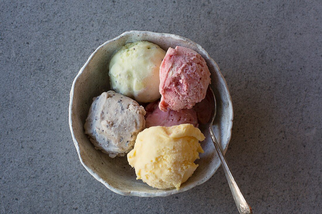 Homemade ice cream (mango, strawberry, blueberry and lime) in a bowl with a spoon
