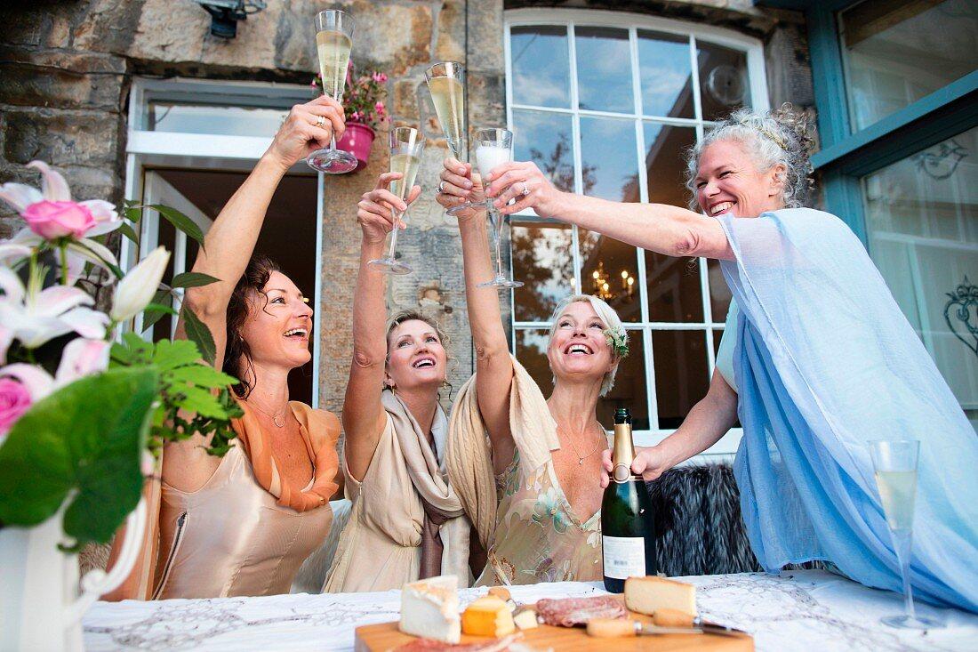 Vier Damen in Abendkleidern stossen mit Sekt an