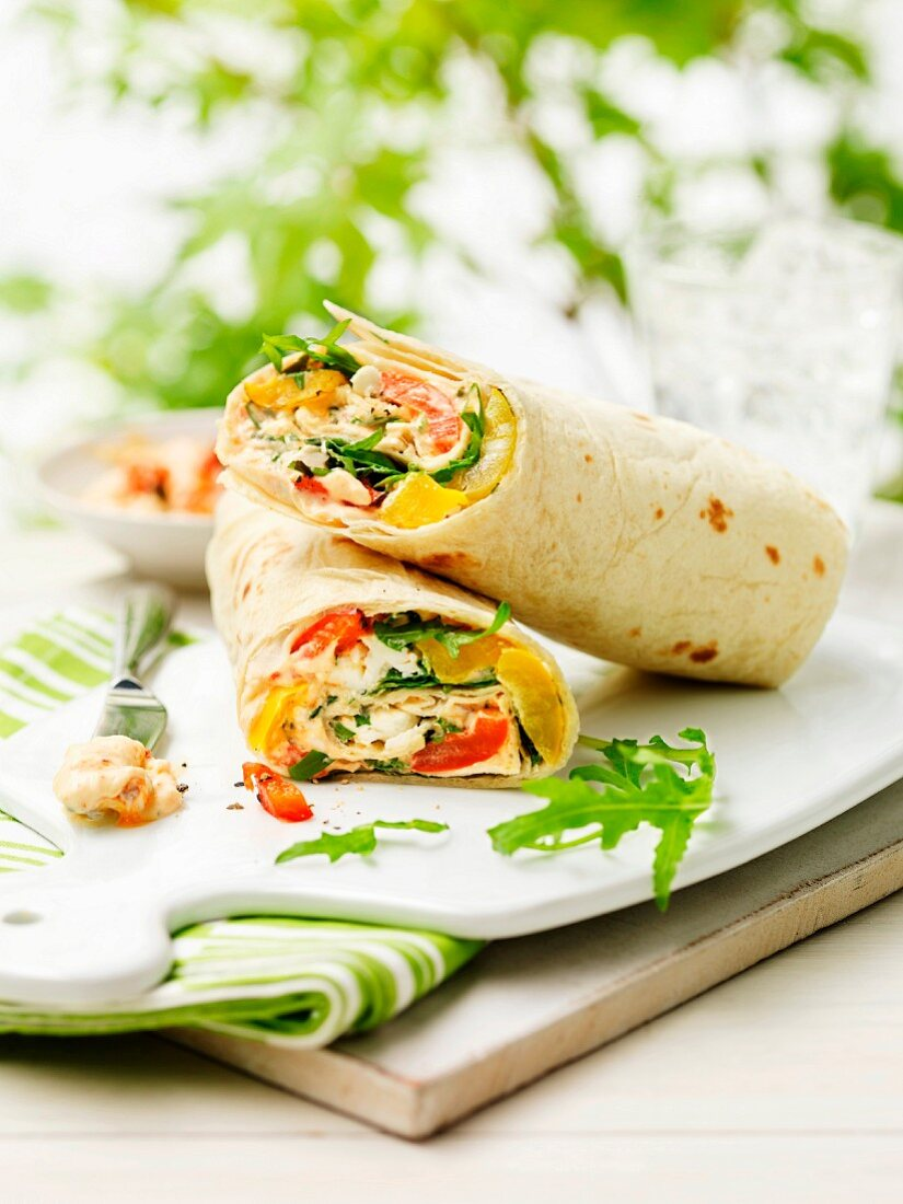 Cheese and salad wraps on a chopping board