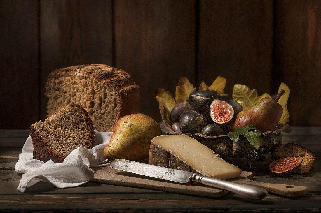 An autumnal arrangement featuring bread, cheese, pears and figs
