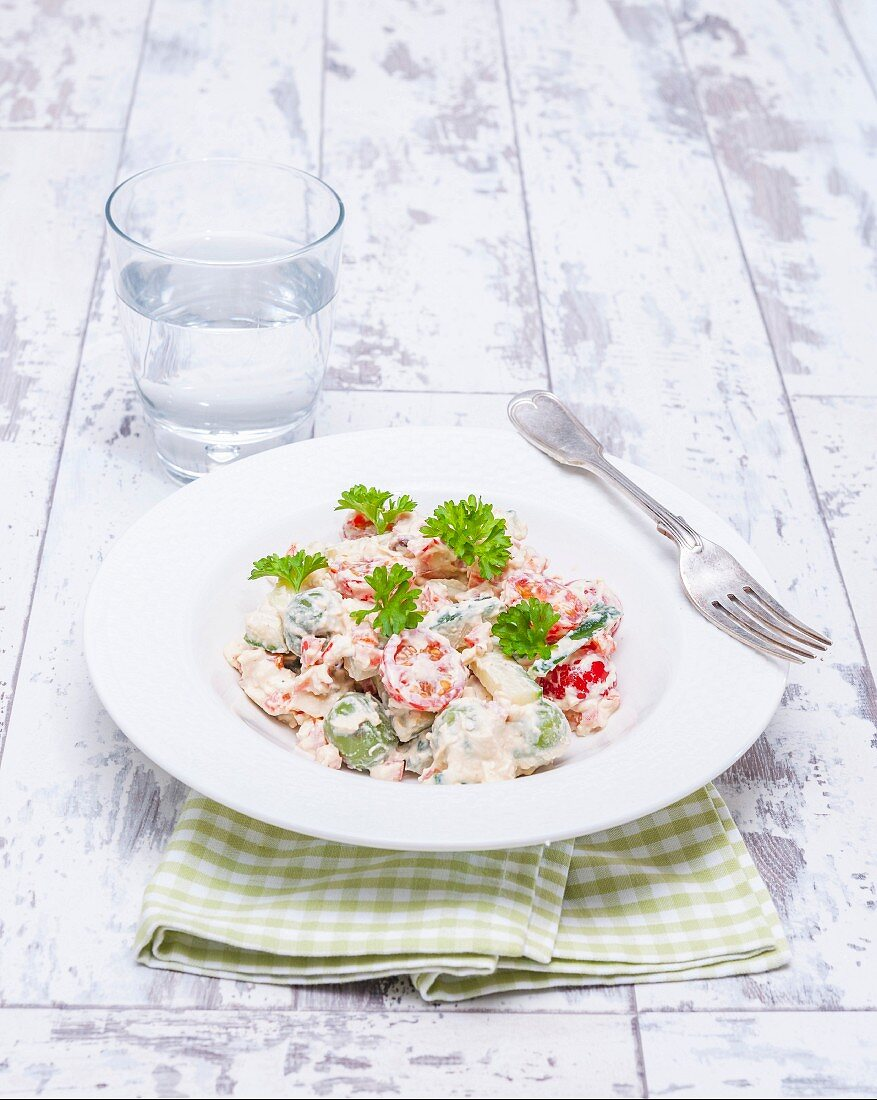 A vegetable dish with cocktail tomatoes and a yoghurt dressing