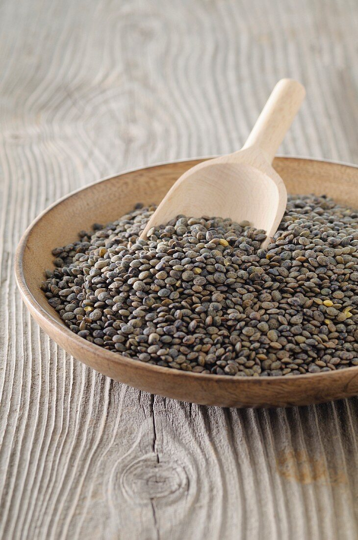 Lentils in a bowl with a wooden scoop