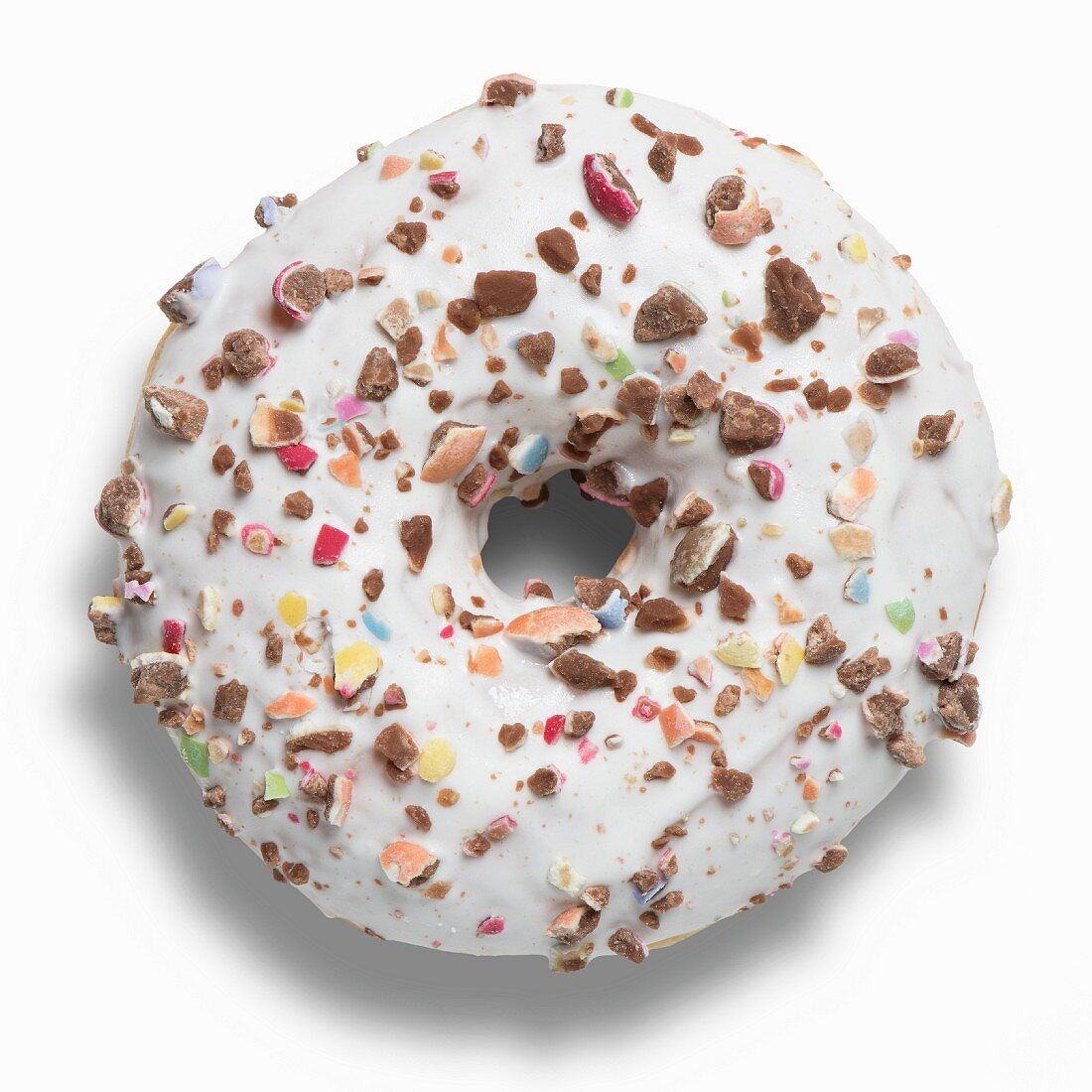 A doughnut with white icing and chopped chocolate beans