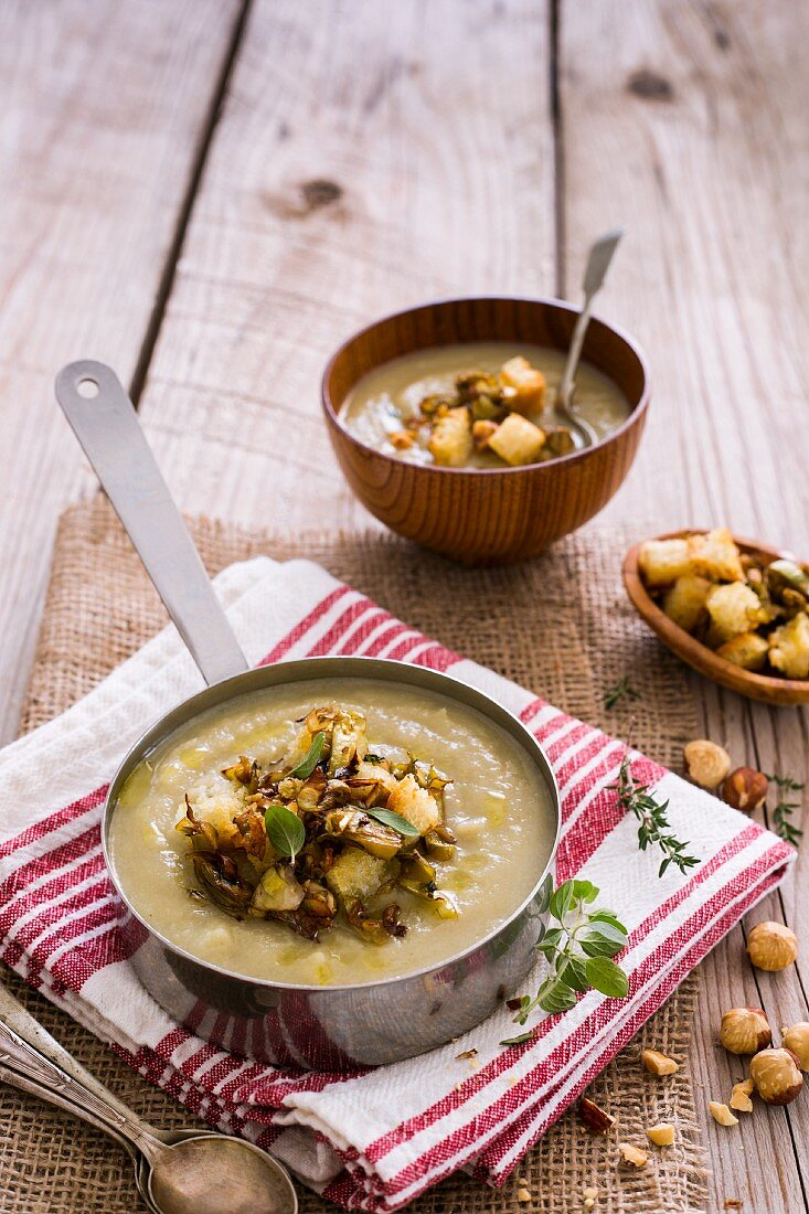 Hearty winter soup with roasted artichokes, hazelnuts and croutons