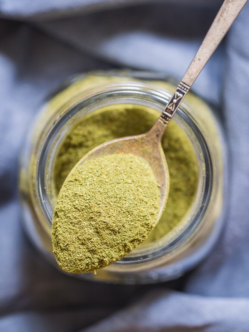 Moringa powder (superfood) on a spoon and in a jar