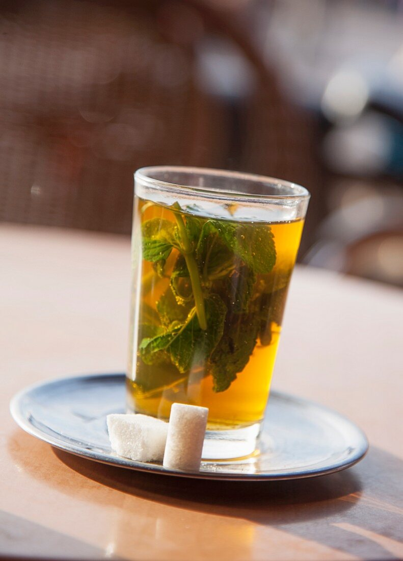 A glass of peppermint tea with sugar lumps