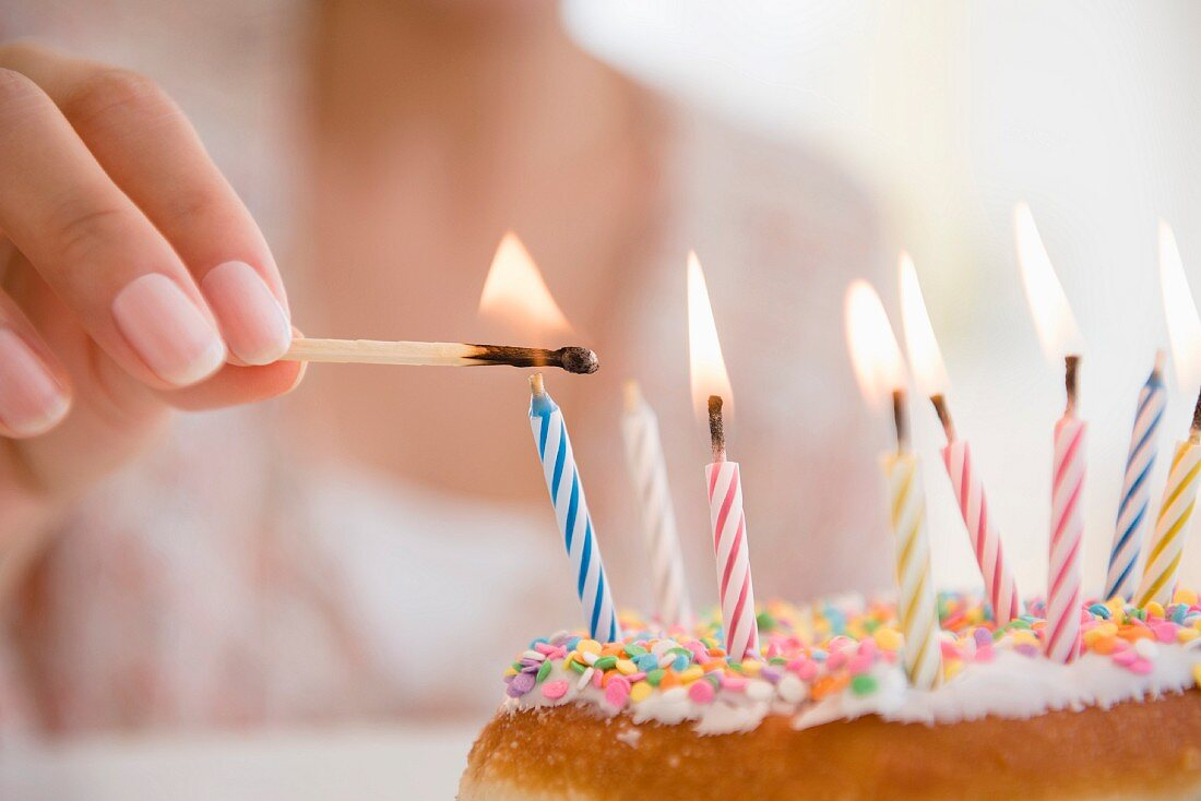 Small candles on a birthday cake being lit