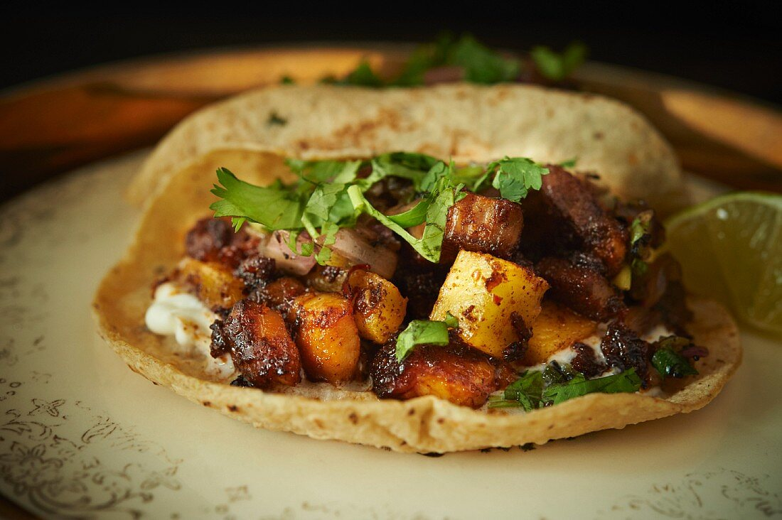 A taco filled with pork belly, grilled fruit and coriander