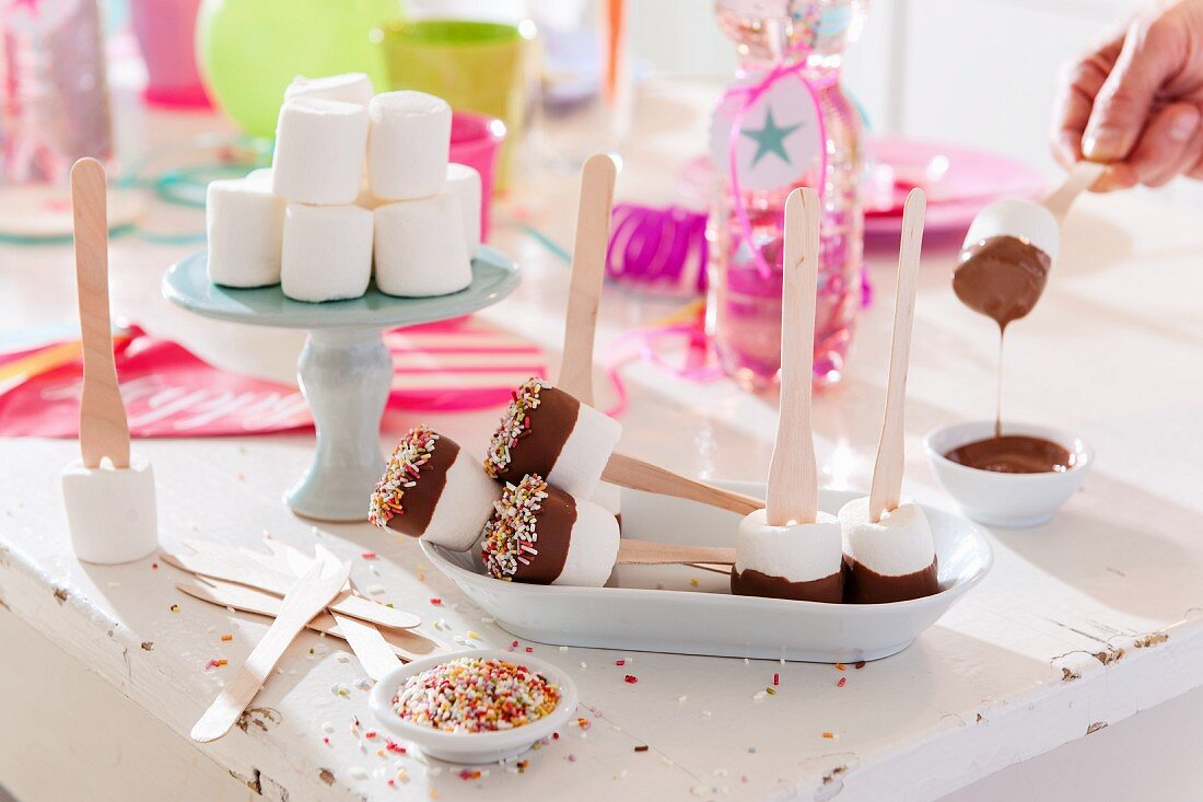 Marshmallows on sticks with chocolate glaze on a table at a birthday party