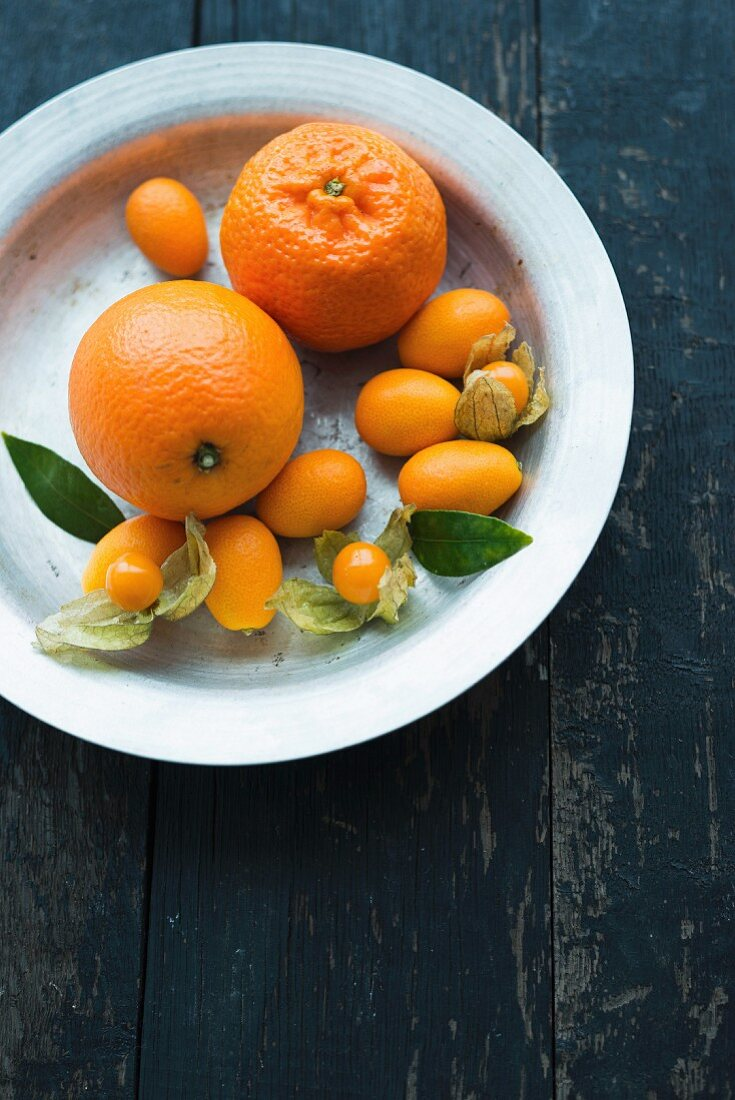 Various citrus fruits and physalis on a plate