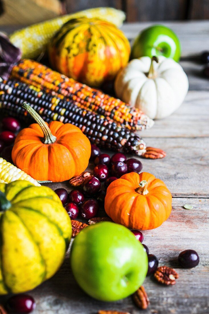 Pumpkins, corn cobs, apples, nuts and cranberries on a wooden surface